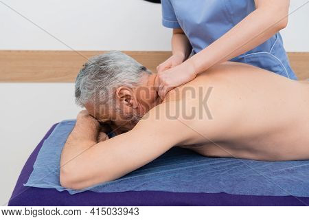 Masseuse Doing Neck Massage To Middle Aged Man In Hospital.