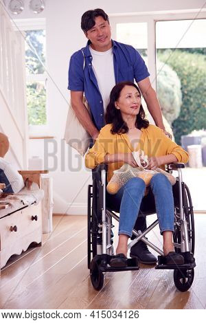 Asian Man Pushing Wife In Wheelchair At Home Back From Shopping Trip With Bag