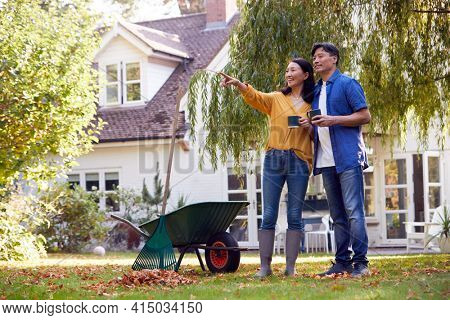 Mature Asian Couple Taking A Break With Hot Drinks Whilst Tidying Garden With Rake And Barrow