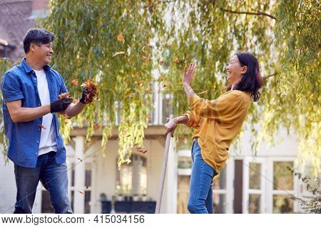 Mature Asian Couple Having Fun Throwing Leaves As They Working In Garden At Home Together