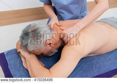 Masseuse Doing Back Massage To Middle Aged Man In Rehabilitation Center.