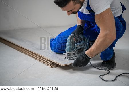 Repairman In Blue Uniform Cuts Laminate With Jigsaw