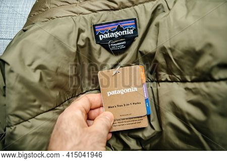 Lyon, France - Feb 16, 2021: Pov Male Hand Reading Tag Of New Parka Duvet Manufactured By Patagonia