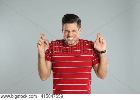 Man With Crossed Fingers On Grey Background. Superstition Concept