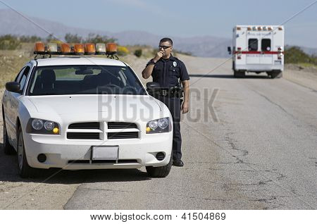 Police officer communicating on radio standing by car