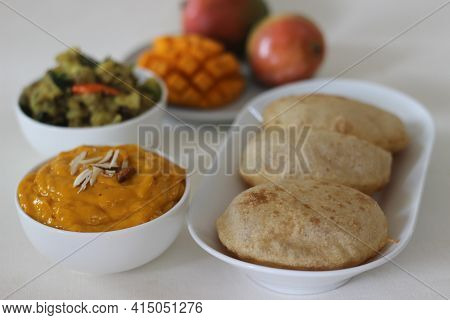 Puri Served With Mango Pulp And Potato Masala. Locally Known As Puri Masala And Aamras.