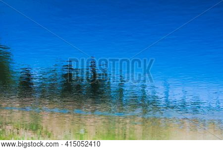 Landscape And Trees Reflected On The Calm Waters Of A Pond.