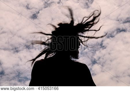 Man Moving His Hair With Dreadlocks With Blue Sky And Clouds In The Background
