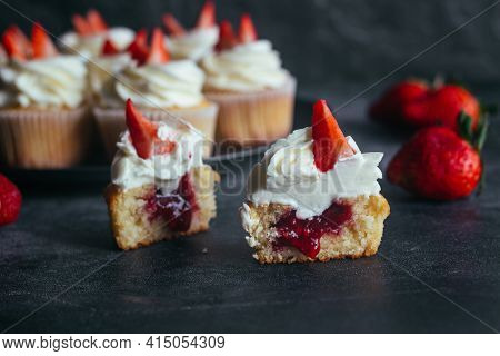 Delicious Cupcakes. Cupcakes With Cream Cheese And Strawberries. Cupcakes On A Concrete Table