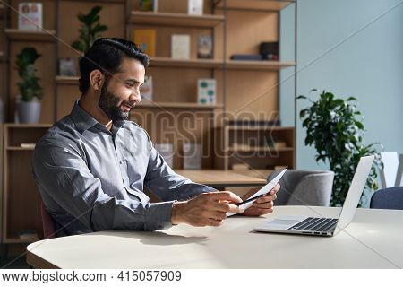 Smiling Indian Business Man Employee Working On Laptop Looking At Document At Home Office. Male Ethn