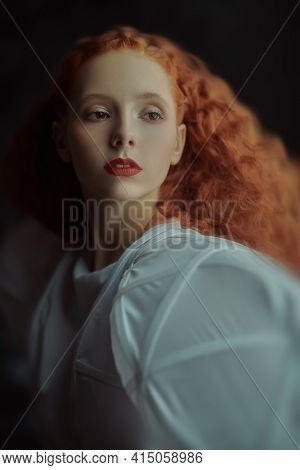 Close up portrait of a refined fashion model girl with lush red curly hair posing in a white haute couture dress in the dark.