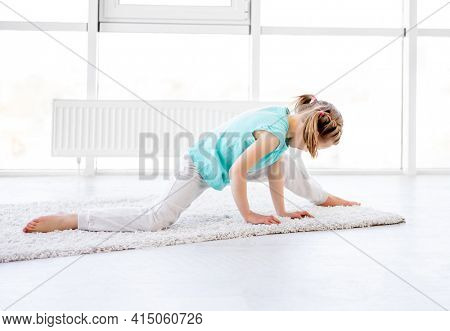 Pretty little girl trying to do twine in bright room