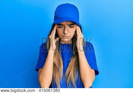 Young hispanic woman wearing delivery uniform and cap suffering from headache desperate and stressed because pain and migraine. hands on head.