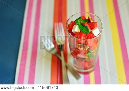 Very refreshing watermelon garnished with walnut, feta cheese and milnt leaves and served in a glass. Healthy and nutritious snacks and salads.