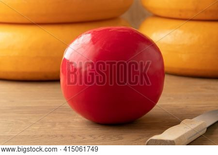 Whole Dutch red Edam cheese on a cutting board and large cheeses at the background