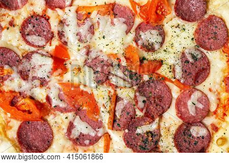 Closeup of pepperoni pizza with salami mozzarella and tomatoes. Top view.