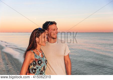 Interracial couple walking on Florida beach watching sunset. Young happy Asian woman and Caucasian man smiling natural beauty outdoor portrait. USA travel vacation.