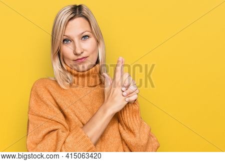 Middle age caucasian woman wearing casual winter sweater holding symbolic gun with hand gesture, playing killing shooting weapons, angry face