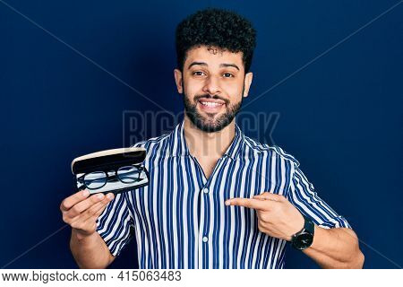 Young arab man with beard holding glasses in eyewear case smiling happy pointing with hand and finger