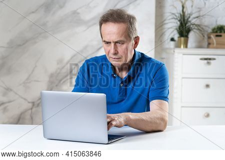 Portrait Of Handsome Senior Elderly Mature Concentrated Man, Working, Using His Laptop Computer, Typ