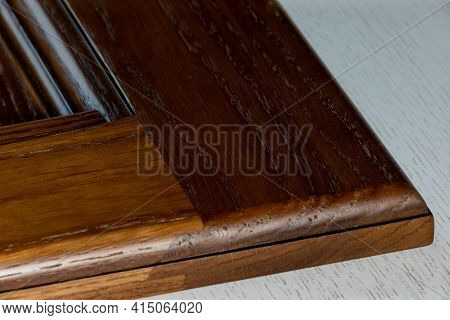 Vintage Texture Of The Bottom Corner Of A Lacquered Classic Facade On A White Table. Background For