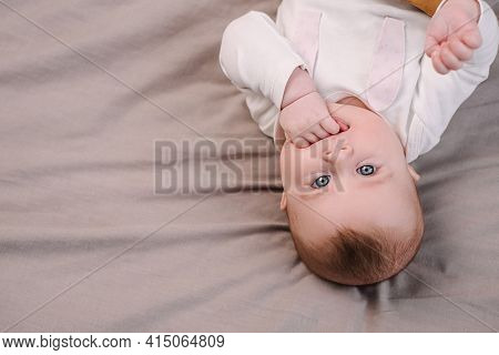Close Up Top View Portrait Of Beautiful Sweet Cute Caucasian Infant Baby Girl With Fingers In Mouth