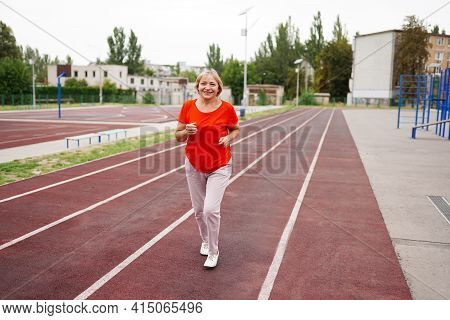 Elderly Woman Running In Early Morning. Attractive Looking Mature Woman Keeping Fit And Healthy.