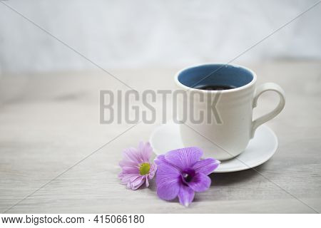 Cup Of Coffee With Flowers. Morning Coffee Concept With Soft Purple Orchid Daisy Flower On White Tab