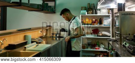Young Chef Is Opening The Kitchen. Asian Cook Putting On An Apron To Getting Starting In The Cuisine