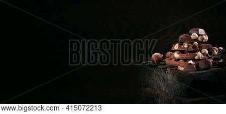 Pile Of Hazelnut Milk Chocolate And Nuts On Dark Wooden Background