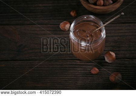 Homemade Chocolate Hazelnut Milk Spread On Glass Jar On Dark Wooden Background