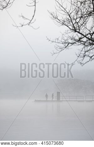 A Foggy Morning On The River Hamble. Two People Almost Lost In Mist Are Visable On A Jetty. There Ar