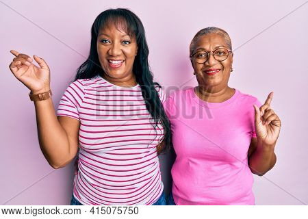 Hispanic family of mother and daughter hugging together with love smiling happy pointing with hand and finger to the side