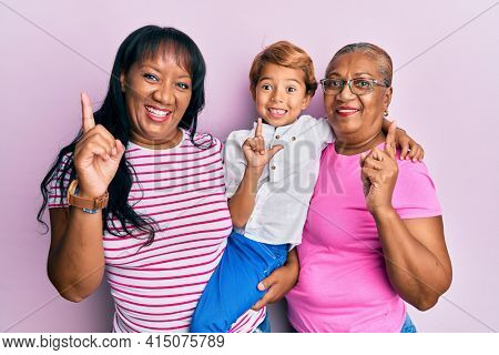 Hispanic family of grandmother, mother and son hugging together smiling with an idea or question pointing finger with happy face, number one