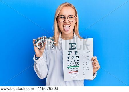 Beautiful caucasian optician woman holding optometry glasses and medical exam sticking tongue out happy with funny expression.