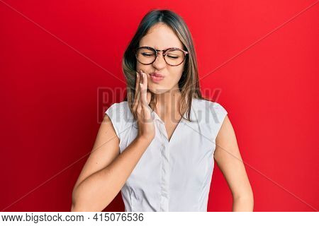 Young brunette woman wearing casual clothes and glasses touching mouth with hand with painful expression because of toothache or dental illness on teeth. dentist