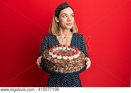 Young caucasian blonde woman holding chocolate cake smiling looking to the side and staring away thinking.