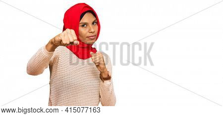 Young african american woman wearing traditional islamic hijab scarf punching fist to fight, aggressive and angry attack, threat and violence