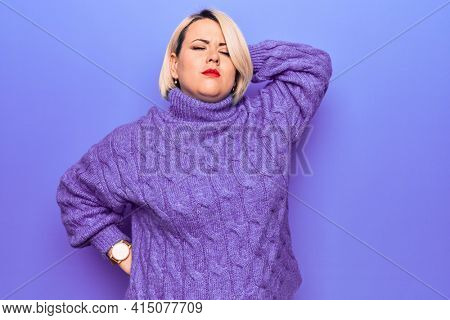 Beautiful blonde plus size woman wearing casual turtleneck sweater over purple background Suffering of neck ache injury, touching neck with hand, muscular pain