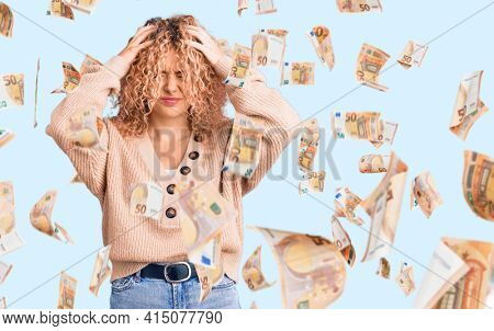 Young blonde woman with curly hair wearing casual winter jumper suffering from headache desperate and stressed because pain and migraine. hands on head.