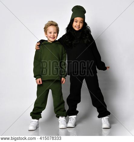 Studio Full-length Portrait Of Little European Boy And Preteen Asian Girl Children Model Wearing War