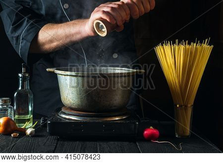 The Chef Prepares Italian Pasta On The Background Of Vegetables. Close-up Of A Cook Hand Pouring Pep