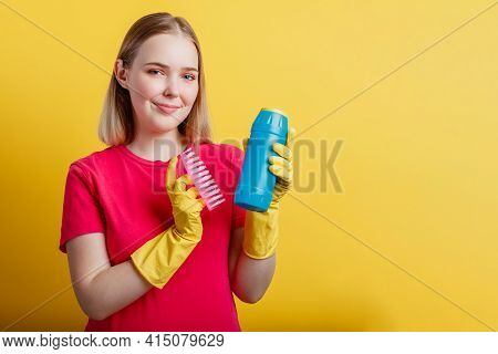 Young Blonde Happy Smiling Woman Ready To Cleaning House With Household Supplies Isolated Over Yello