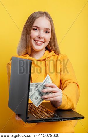 Beautiful young woman freelancer takes out dollars money banknotes from laptop. Win in online casino game wealth by freelancer work. IT remote work via laptop isolated over yellow color background