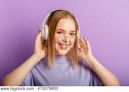 Young woman in headphones with beautiful smile blonde hairstyle portrait. Teenager girl enjoy listen song music moving in headphones isolated over purple color background