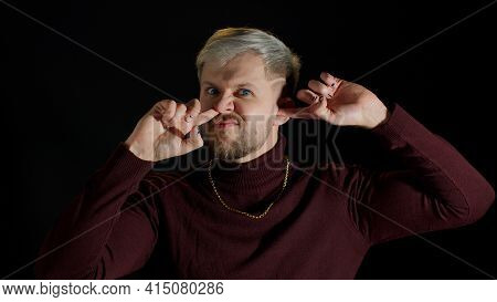 Funny Stupid Stylish Young Man With Blue Eyes Picking Nose And Ear With Silly Smiling Humorous Expre