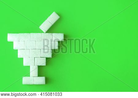 A Glass With A Drink Is Laid Out From Sugar Cubes On A Green Background. An Idea Of The Dangers Of C