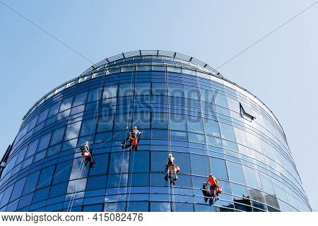 Window Cleaners Wash Blue Mirrored Windows Outside The Building.