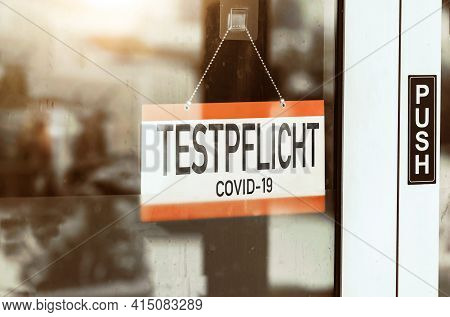 Testpflicht, Translated: - Mandatory Testing Sign Hangs On The Door Of A Store. Corona Virus Covid-1