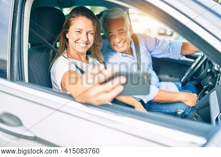 Middle age couple in love sitting inside the car going for a trip taking a selfie picture with smartphone smiling happy and cheerful together